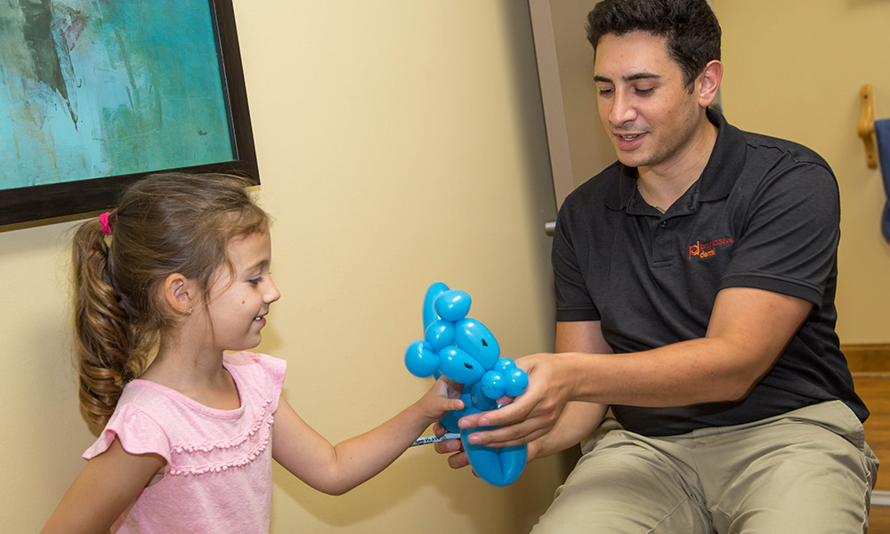 Dr. Spera giving a balloon animal to a young patient