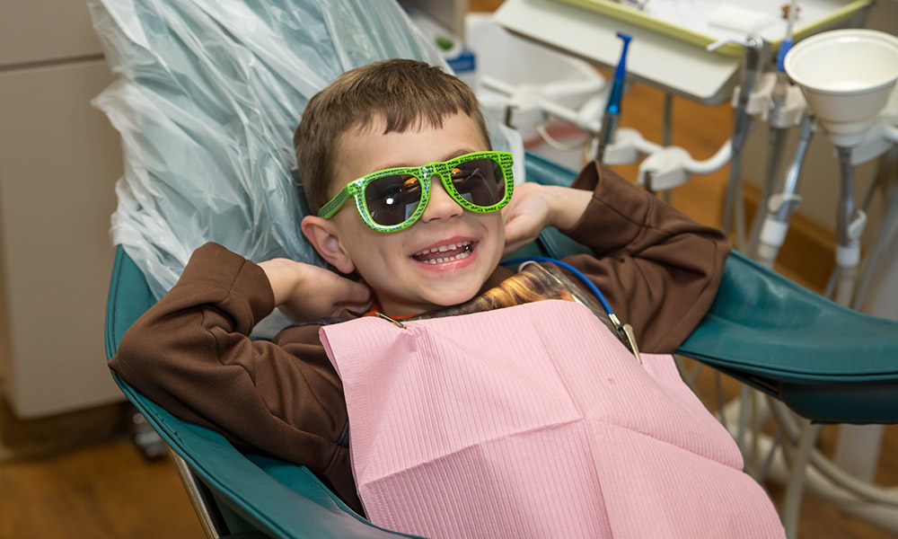 Young patient hanging out on the dental chair with sunglasses on