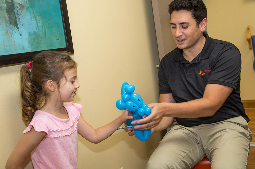 Dr. Marcus Spera giving a little girl a balloon animal after her visit