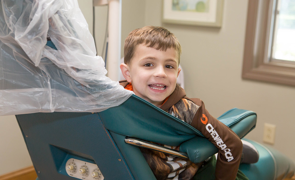 Young patient sitting in an exam chair smiling